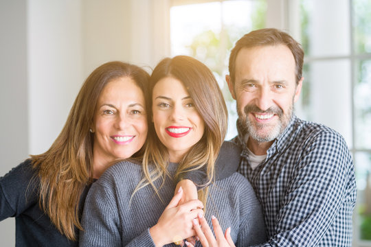 Beautiful family together. Mother, father and daughter smiling and hugging with love at home.