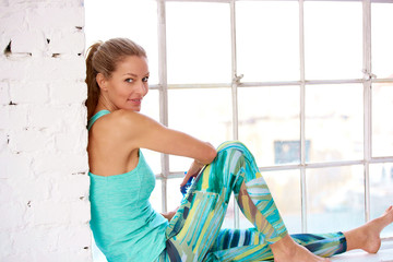 Beautiful woman relaxing after workout while looking at camera and smiling