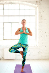 Full length portrait of beautiful woman standing in yoga pose in one leg on yoga mat.