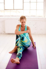 Beautiful woman stretching while sitting on yoga mat after practicing yoga