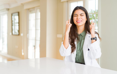 Young woman wearing medical coat at the clinic as therapist or doctor smiling crossing fingers with hope and eyes closed. Luck and superstitious concept.
