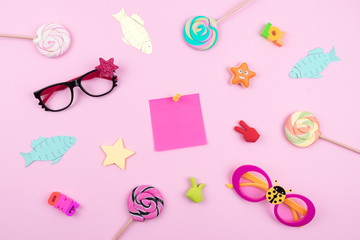 Festive funny celebration background with paper fish, sticky note and decor on pink background. All Fools' Day, humor, prank, joke concept.