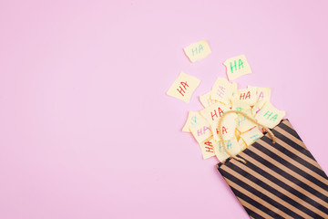 April Fools' Day celebration background. Paper bag with many paper sheets with the words haha. 1 April mockup on pink background. All Fools' Day, humor, prank, joke concept. Wall mural