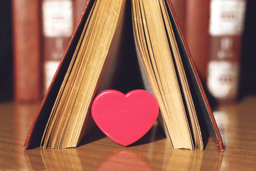 Open book with coral heart on the bookshelf background. Pink plastic Heart in the pages of the book.  Education, literature, knowledge, love background