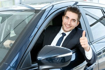 Thumbs up. Portrait of a happy businessman showing thumbs up sitting in his new car