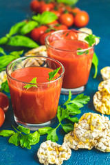 Red cocktail with tomato juice between tomatoes, basil, parsley and nutritious cereal breads
