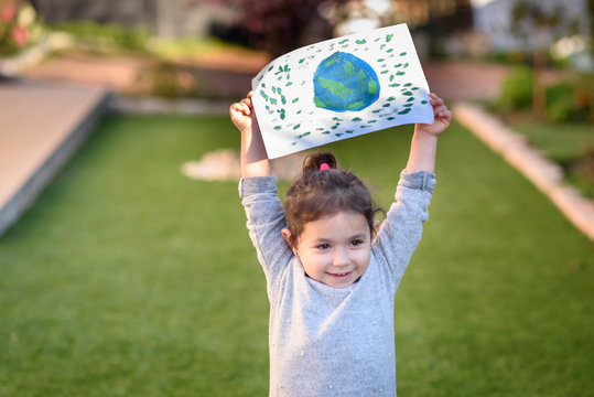 Portrait of the cute little girl holding the drawing earth globe outdoor sunny day. Child painting a picture of earth.Earth day, plastic free and zero waste concept.