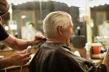 Senior man laughs while getting his hair cut
