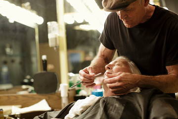 Barber uses a straight razor to shave senior man's face