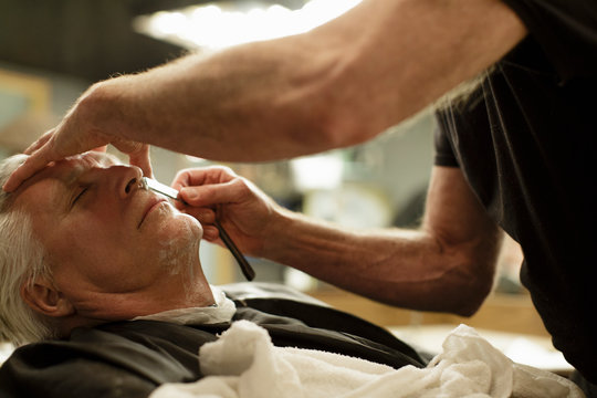 Barber shaves senior man's face with a straight razor