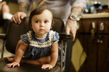 Toddler sits in barbershop chair