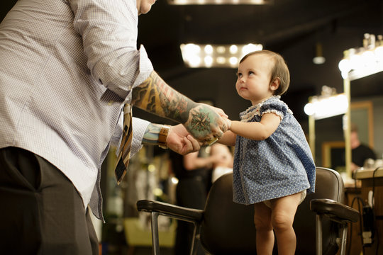 Toddler holds barber's hands and stands in chair