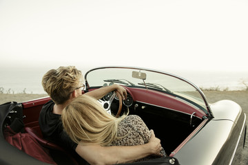 Young man with arm around young woman while they sit in convertible