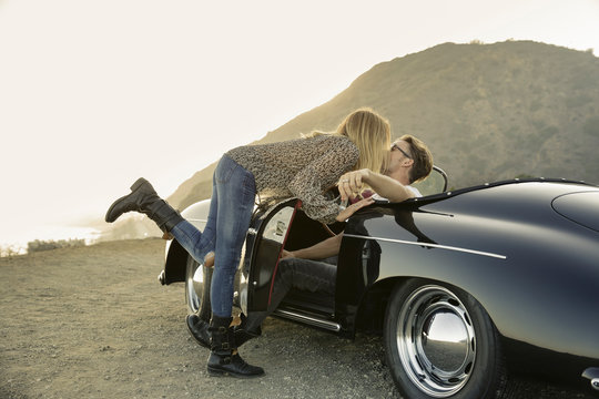 Young woman leans over to kiss young man in convertible