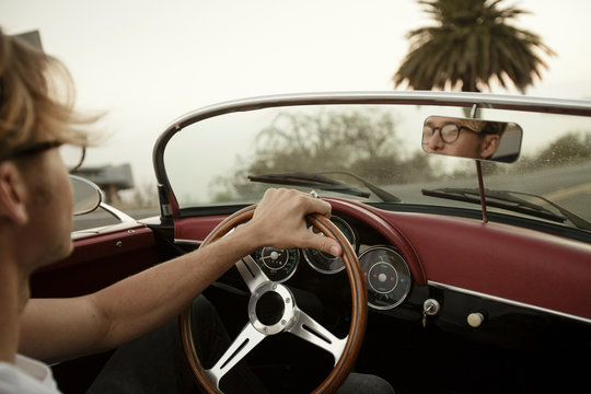 Young man looks in rearview mirror while driving