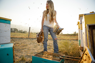 Woman beekeeper stand by hive boxes and smiles while bees fly around