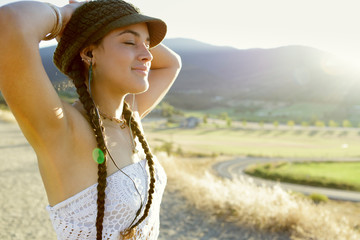 Close up of young woman with braids and knit cap