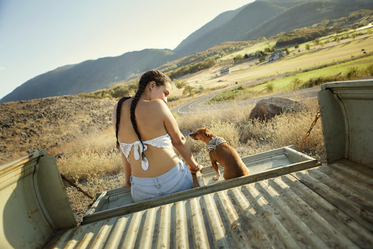 Young woman sits on tailgate with her pet chihuahua