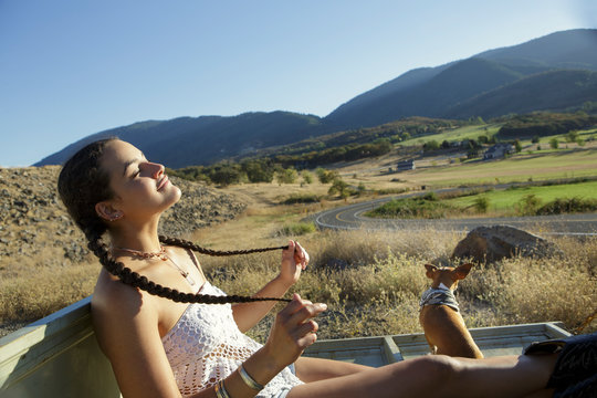 Young woman with braids relaxes in sun with her dog
