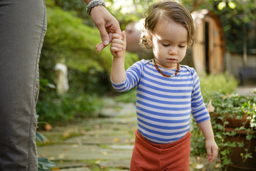 Toddler walks while holding mother's fingers