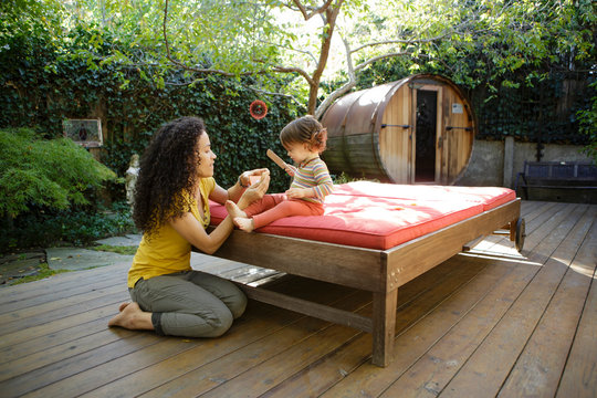 Mother and toddler play with toys on wooden deck