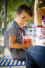 Young boy with a mohawk drinks through a straw