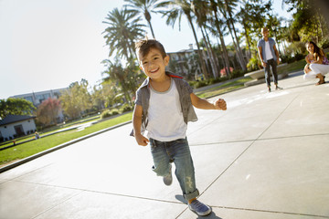 Young boy runs across pavement while parents look on