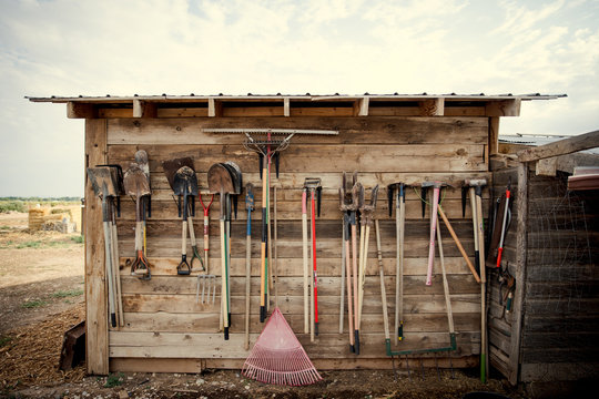 Farm tools hanging on a wood shed