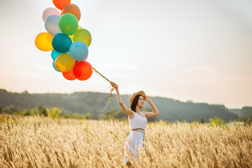 Girl with colorful air balloons in a rye field