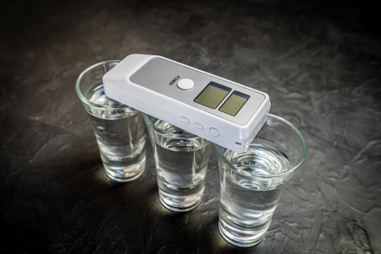 breathalyzer and alcohol in a glass. photo on a dark background.