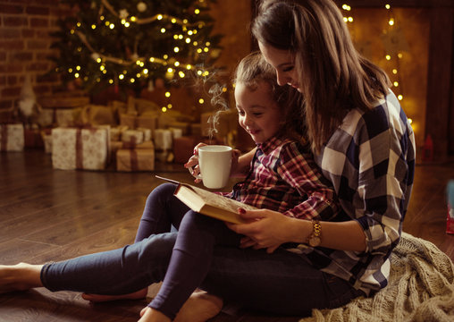 Mother reading a book for her daughter in a calm, winter eveneing