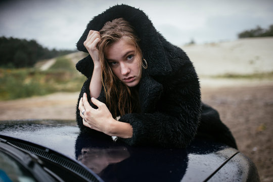Portrait of young woman in black fur coat leaning on car bonnet