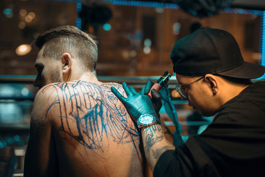 Side view of male tattoo artist tattooing client in parlor