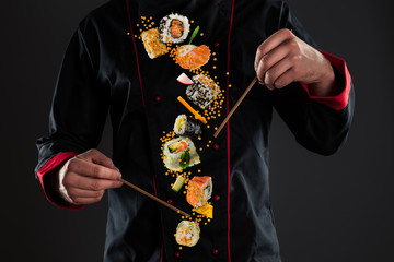 Master chef holding chopsticks with flying sushi