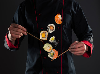 In de dag Sushi bar Master chef holding chopsticks with flying sushi