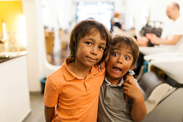 Two little boys smiling in a hair salon