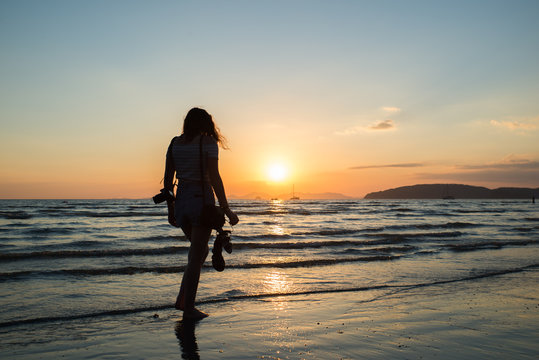 Girl walking and relaxing at sunset on a tropical beach in Thailand