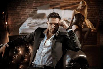 Photo sur Aluminium Artiste KB Handsome man relaxing in the luxurious apartment with a sensual woman
