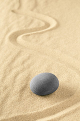 Healing treatment or spiritual therapy trough relaxation and meditation concentrating on a zen stone garden. Spa wellness background with sand texture.
