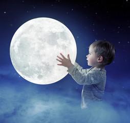 Art portrait of a cute little boy holding a moon
