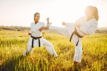 Two female karate in kimono training combat skill