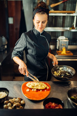 Female chef with pan cooking meat with pasta