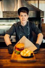 Chef in gloves and uniform cuts juicy steak piece