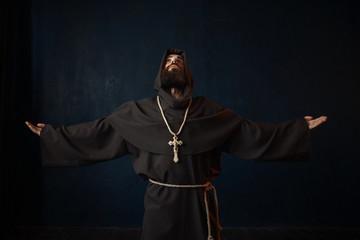 Monk in black robe with hood kneeling and praying