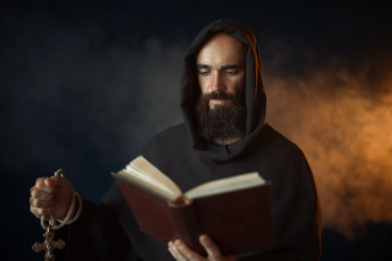 Medieval monk praying with book in church