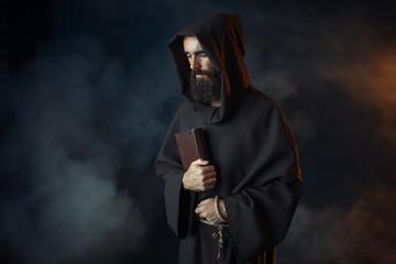 Fototapeta Medieval monk in robe holds spellbook in hands