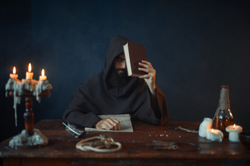 Medieval monk sitting at the table and reads