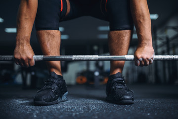 Powerlifter prepares for deadlift a barbell in gym