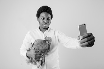 Young excited dark skinned african american smiling man with cock in hands take selfie in studio on white background. Black adult happy nigerian male with rooster make selfie with phone. Pet lover.