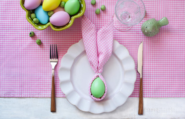 Festive Easter table setting with napkin Easter Bunny, top view.